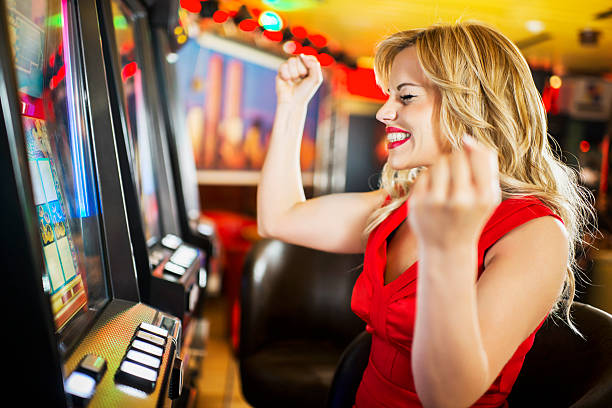 Ecstatic woman winning money on a slot machine in a casino.